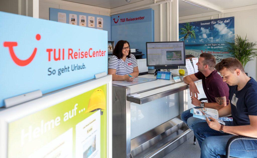 Kunden lassen sich im am Counter des TUI Reisecenter beraten.