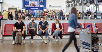 Wartende Passagiere mit Maske am Flughafen Memmingen vor den Check-in Schaltern.