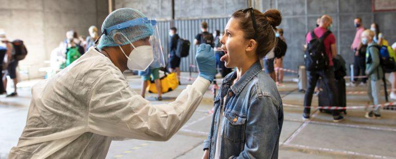 Mitarbeiter von EcoCare macht einen Coronatest bei einem Passagier